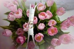 Rosa tulpan i korgen med vigselringar Arkivbild