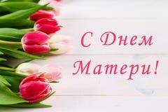 Rosa tulpan på en vit trätabell med en inskrift i ryss - lycklig dag för moder` s royaltyfria foton