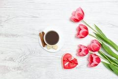 Rosa tulpan, rånar av kaffe och den röda pepparkakan Ljus träbac Royaltyfria Foton