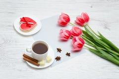 Rosa tulpan, rånar av kaffe och den röda pepparkakan Ljus träbac Royaltyfri Bild
