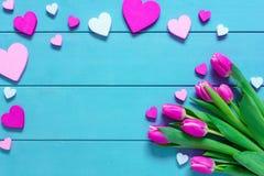 Rosa tulpanblommor och hjärtor på den blåa trätabellen för mars 8, internationella kvinnors dag, födelsedagen, valentindagen elle Arkivfoton