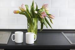 Rosa tulpanbukett i den glass vasen på köket royaltyfria foton