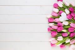Rosa Tulpe auf dem weißen Hintergrund Rote Tulpe und farbige Eier stockfotos