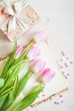 Rosa Tulpen mit Geschenkbox über weißem Holztisch Stockbild