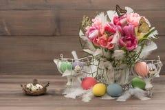Rosa Tulpen, Schmetterlinge und farbige Ostereier Stockbild