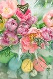 Rosa Tulpenblumen, Schmetterlinge und farbige Eier Stockbild
