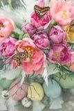 Rosa Tulpenblumen, Schmetterlinge und farbige Eier Stockbilder
