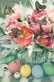 Rosa Tulpenblumen, Schmetterlinge und Ostereier Stockbild