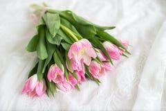 Rosa Tulpenblumenstrauß auf weißer Spitze Lilien des Tales und der Hyazinthen auf einem grünen Hintergrund der Blätter lizenzfreies stockfoto