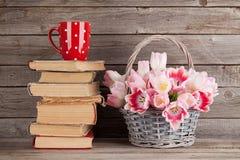 Rosa Tulpenblumenstrauß, Bücher und Kaffeetasse Lizenzfreie Stockfotos