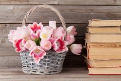 Rosa Tulpenblumenstraußkorb und alte Bücher Lizenzfreie Stockfotos