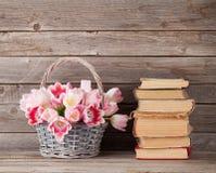 Rosa Tulpenblumenstraußkorb und alte Bücher Stockfotos