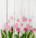 Rosa Tulpenblumenstrauß mit Papierherzen auf hölzernem Hintergrund Stockfotos