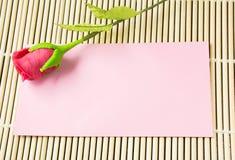 Rosa Umschlag mit künstlicher Rotrose Stockfotografie