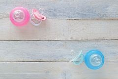 Rosa und blaue Friedensstifter und Babyflaschen auf weißem Holz lizenzfreie stockfotos