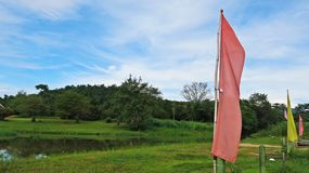 Rosa und gelbe Flagge mit Land des grünen Grases und Hintergrund des blauen Himmels Stockbilder