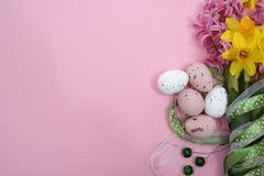 Rosa und gelbe Frühlingsblumen, farbige Eier mit grünem Band, Stockfotografie