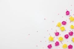 Rosa und gelbe Rosen, die auf einem weißen Hintergrund übersteigen stockbild