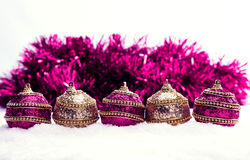Rosa und Purpur und Goldweihnachtsbälle im Schnee mit Lametta, Weihnachtshintergrund Lizenzfreies Stockfoto