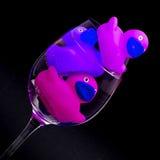 Rosa und purpurrote Gummienten in den Weingläsern stockbilder
