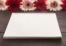 Rosa und rote Gerberablumen mit Notizbuch sind im hölzernen Hintergrund Stockfotografie
