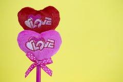 Rosa und rote Herzen auf gelbem Beschaffenheitshintergrund, Valentinstag Stockfotografie