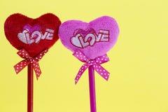 Rosa und rote Herzen auf gelbem Beschaffenheitshintergrund, Valentinstagkartenkonzept Stockfotos