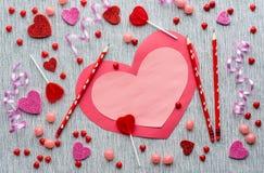 Rosa und rote Valentinsgrußkarte mit Bleistiften und Süßigkeit auf grauem Hintergrund Stockbild