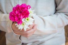 Rosa und weiße Blumen in den Händen der Frauen Stockfotos