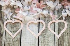 Rosa und weiße Herzen und Blumen auf einem Holztisch Stockfotografie