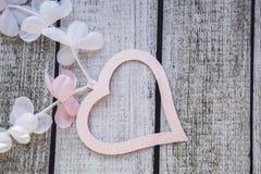 Rosa und weiße Herzen und Blumen auf einem Holztisch Lizenzfreies Stockfoto