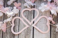 Rosa und weiße Herzen und Blumen auf einem Holztisch Stockbilder