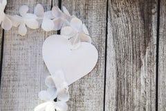 Rosa und weiße Herzen und Blumen auf einem Holztisch Lizenzfreie Stockbilder