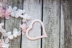 Rosa und weiße Herzen und Blumen auf einem Holztisch Stockfoto