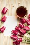 Rosa und weiße Tulpen mit Tee und klarer Postkarte Lizenzfreies Stockfoto