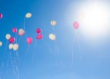 Rosa und weiße Ballone, die in den Himmel fliegen Stockfotos