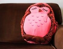 rosa välfylld uggla på den bruna soffan Arkivbild