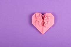 Rosa valentinorigami på en lila bakgrund Hjärta av papper Royaltyfria Bilder