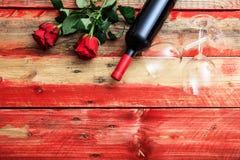 Rosa vermelha Garrafa, vidros e rosas de vinho tinto no fundo de madeira Imagens de Stock Royalty Free
