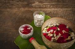 A rosa vermelha, o jasmim e o arroz estalado na superf?cie calma da ?gua colocada na tabela de madeira pronta para derramam a ?gu imagens de stock