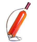 Rosa vinflaska i ställningen som isoleras på vit bakgrund Fotografering för Bildbyråer