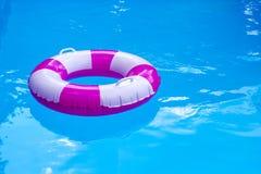 Rosa-weißer Swimmingpoolring, Floss, wenn blaues Wasser erneuert wird Sonniger Tag am Erholungsort Lizenzfreies Stockbild