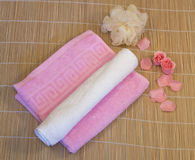 Rosa, weißes Tuch mit dem Blumenblatt auf Bambusmatte lizenzfreies stockbild