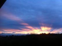 Rosa Wolken über dem Stadt- und Sonnenlichteffekt Stockbilder