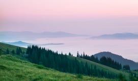 Rosa Wolken über den Bergen am Morgen lizenzfreie stockfotos