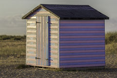 Rosa y choza rayada azul de la playa en la salida del sol Foto de archivo libre de regalías