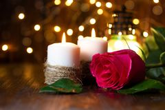 Rosa y linterna rojas con las luces en una tabla de madera imagenes de archivo