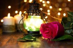 Rosa y linterna rojas con las luces en una tabla de madera fotografía de archivo
