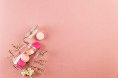 Rosa y macarons o macarrones franceses magentas, bajando de un tarro de cristal con las flores blancas sobre un fondo rosado fotografía de archivo