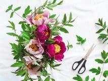 Rosa y peonías púrpuras en un florero en una tabla blanca foto de archivo libre de regalías